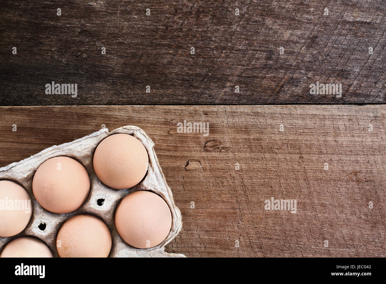 Farm fresh organic brown chicken eggs from free range chickens with in a paper carton over a rustic wooden background. - Stock Image