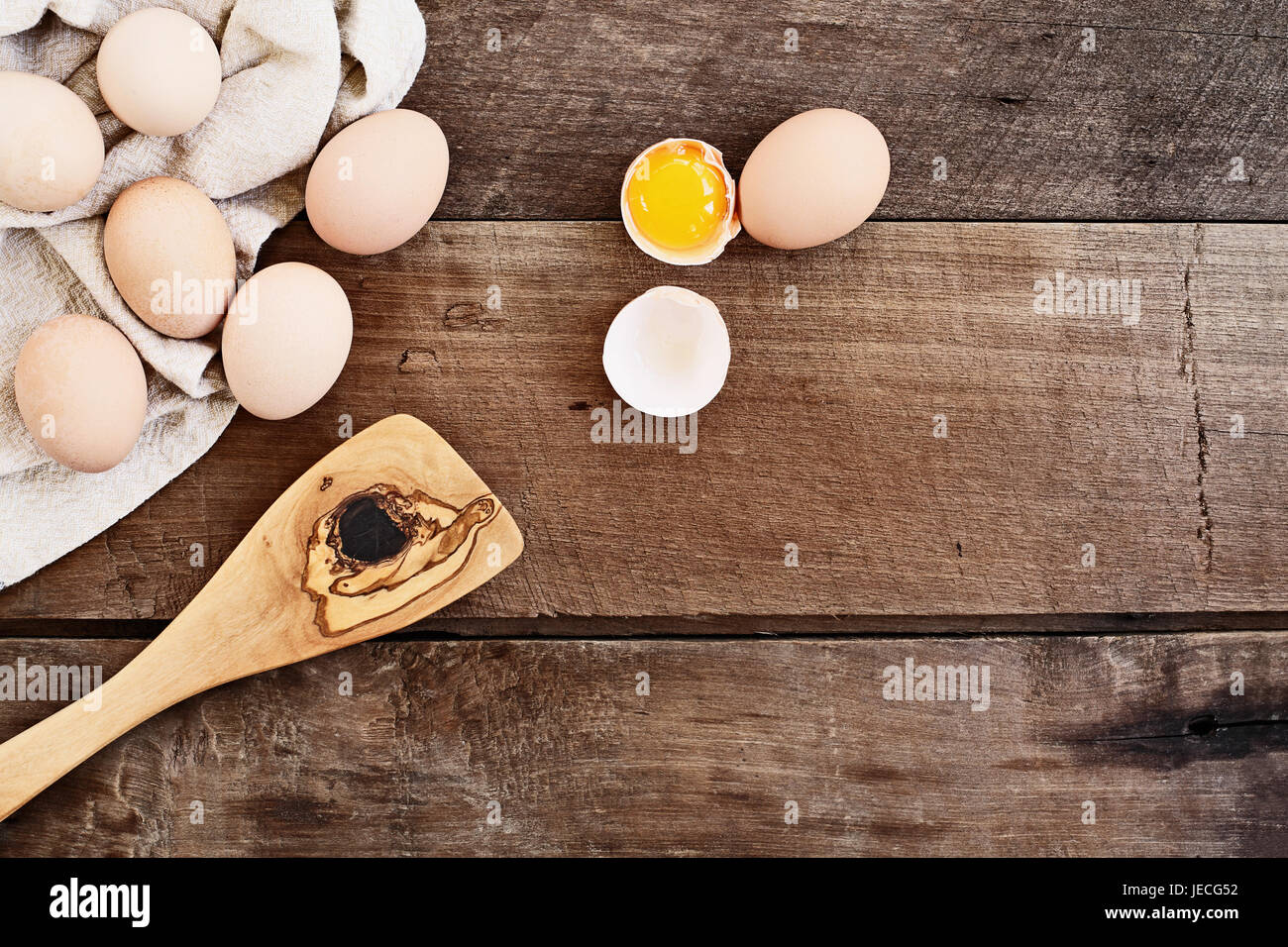 Farm fresh organic brown chicken eggs from free range chickens with an old olive wood antique spatula over a rustic Stock Photo