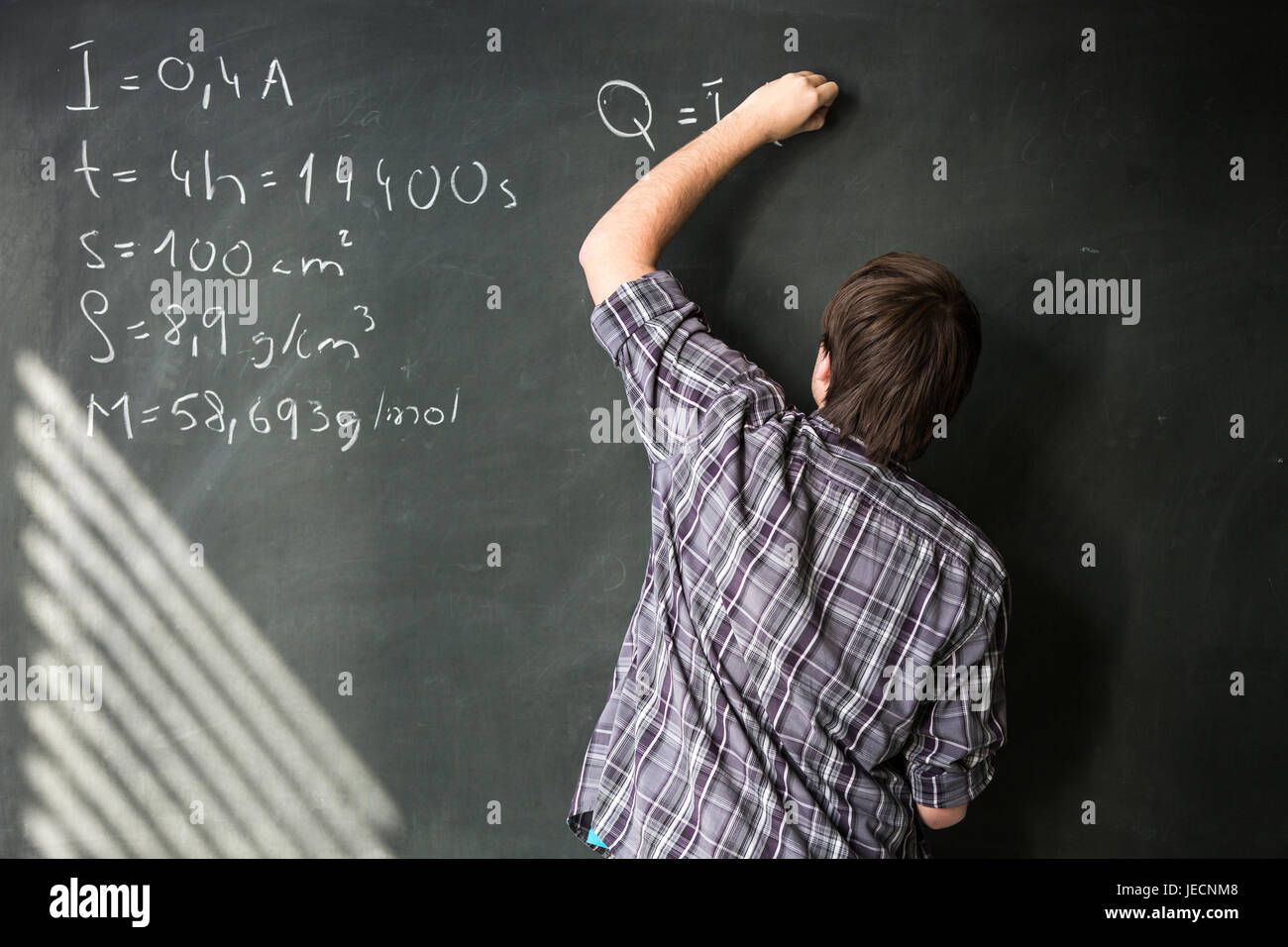 College student solving a math problem during math class in front of ...