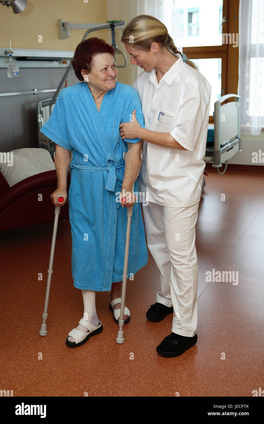 Clinic, physiotherapist, patient, senior, crutches, in need of care, lead, help, walking practise, eye contact, - Stock Image