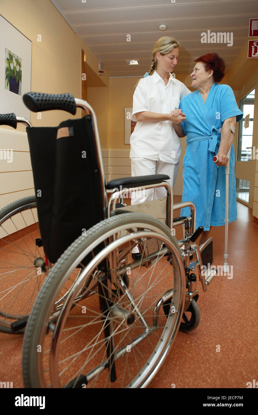 Clinic, hall, physiotherapist, patient, senior, crutches, in need of care, lead, help, walking practise, eye contact, - Stock Image