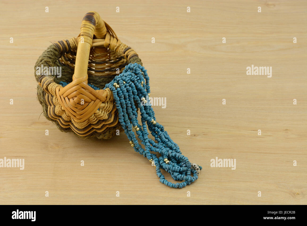 Blue necklace for work draped over handwoven wooden basket at end of day when changing from work clothes to informal - Stock Image