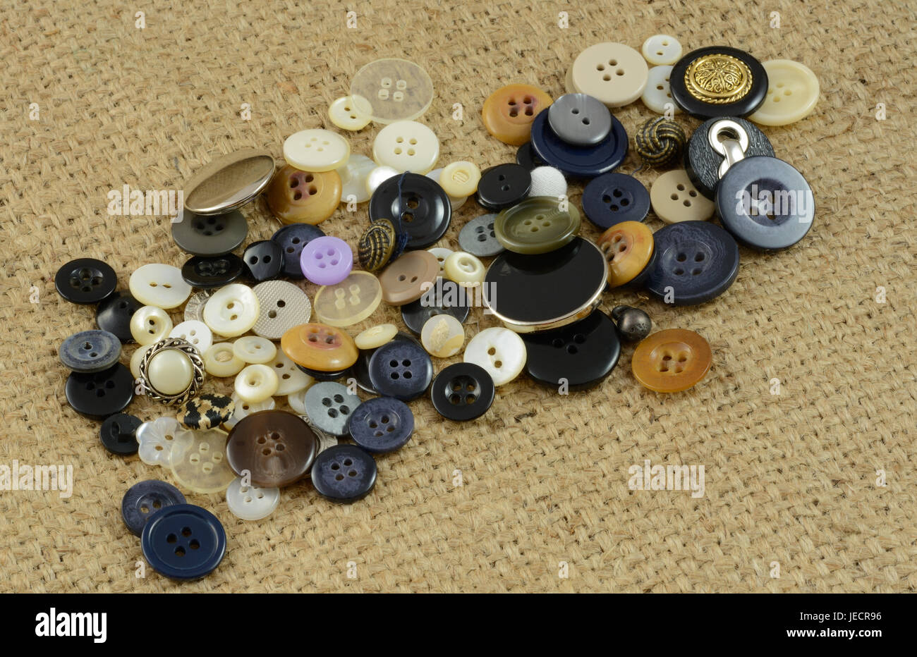 Collection of buttons for crafting or sewing projects on burlap Stock Photo