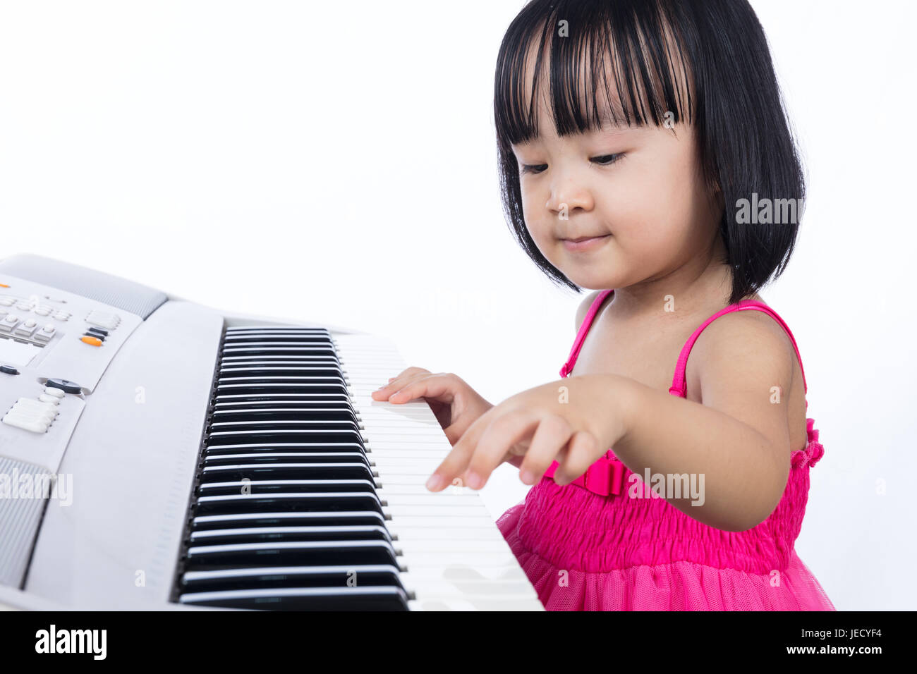 Asian Chinese little girl playing electric piano keyboard in the living room at home. - Stock Image
