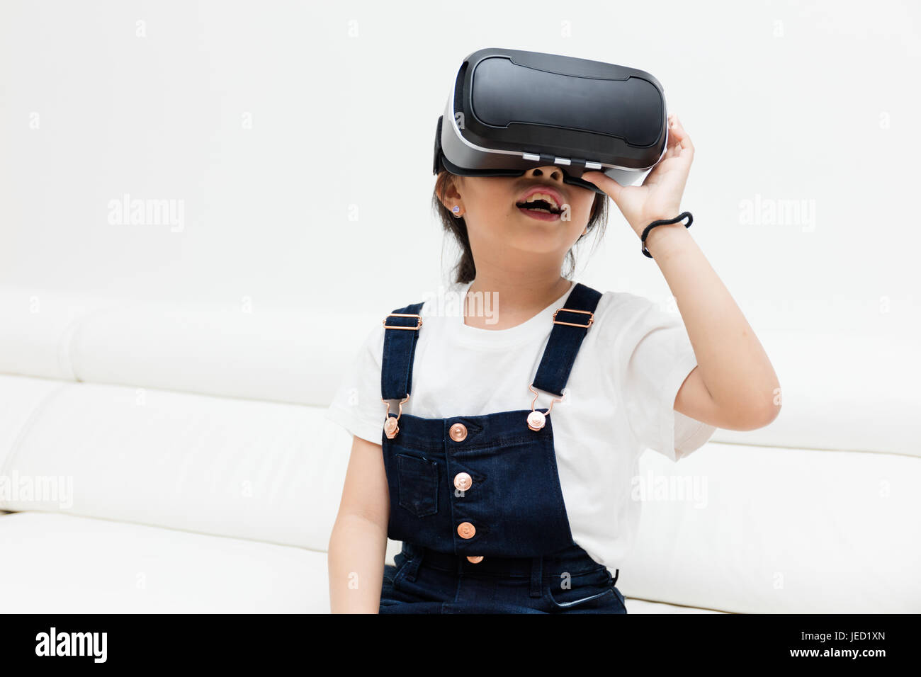 ff11b46dc6d Asian Chinese little girl experiencing virtual reality with vr headset at  home - Stock Image