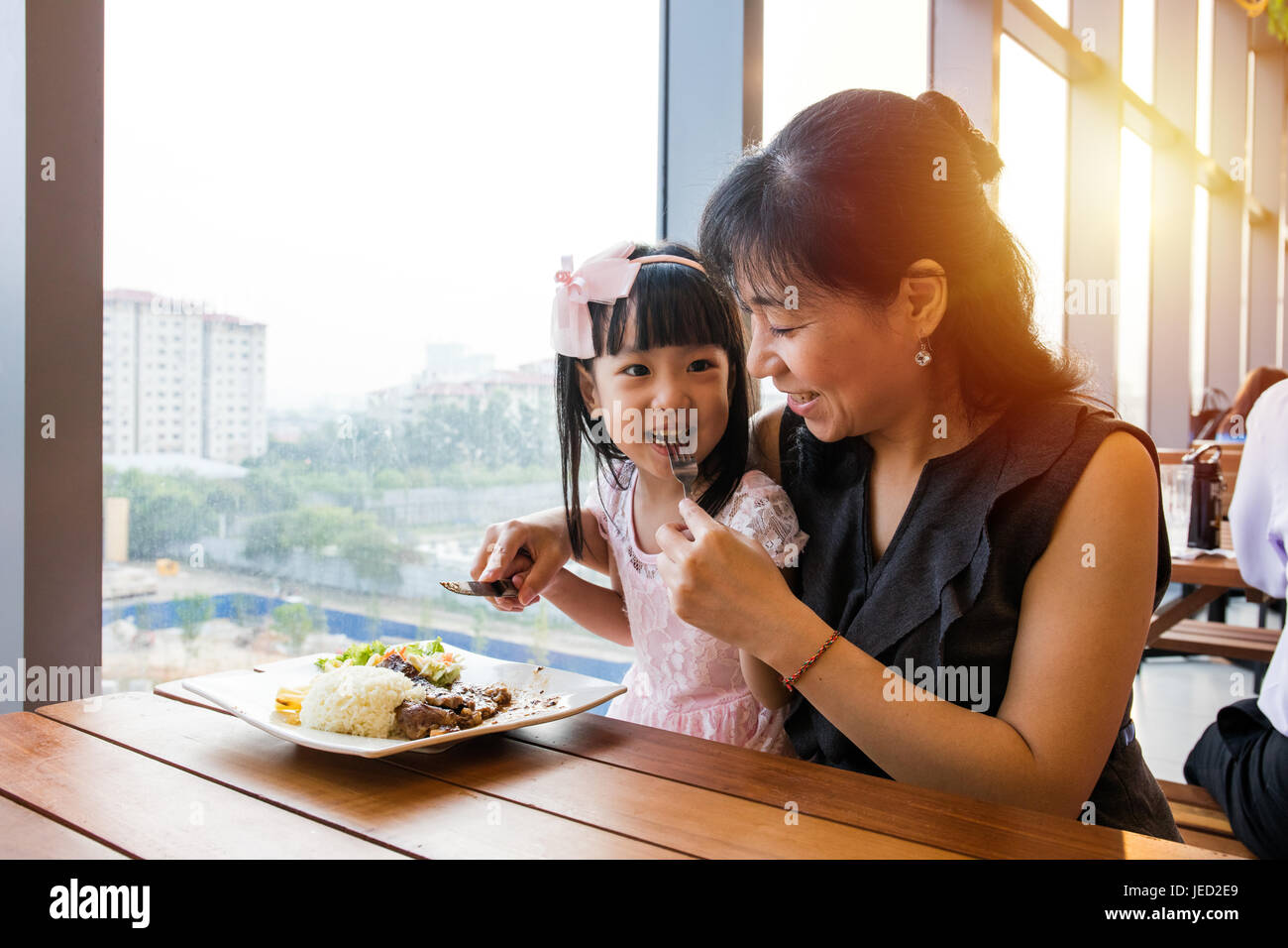 Asian Chinese mother and daughter eating steak in the restaurant. - Stock Image