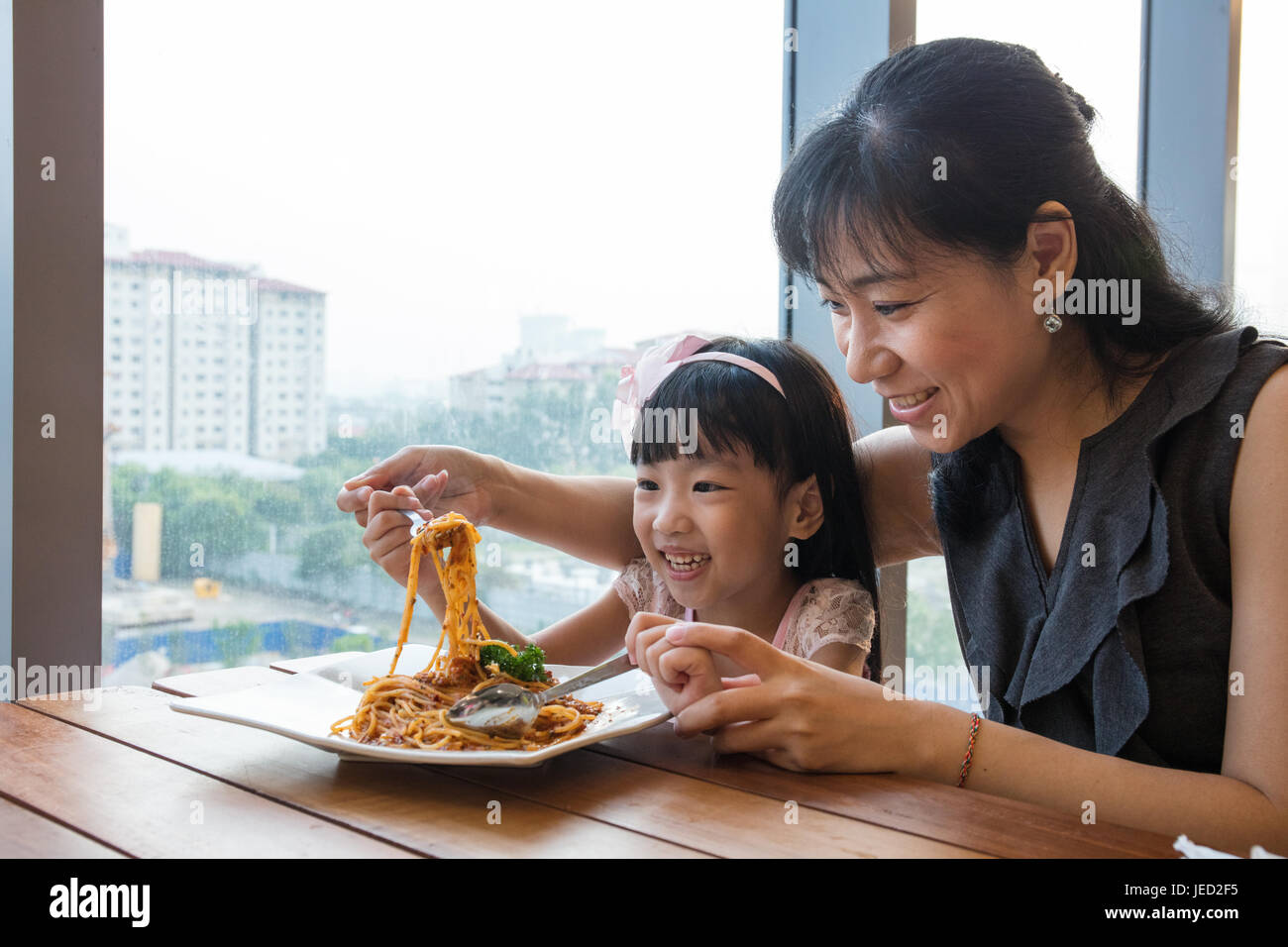 Asian Chinese mother and daughter eating spaghetti bolognese in the restaurant. - Stock Image
