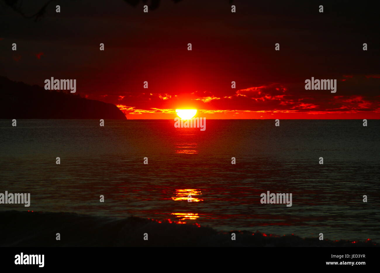 Red sunset bounces off the coast of Mahe - Stock Image