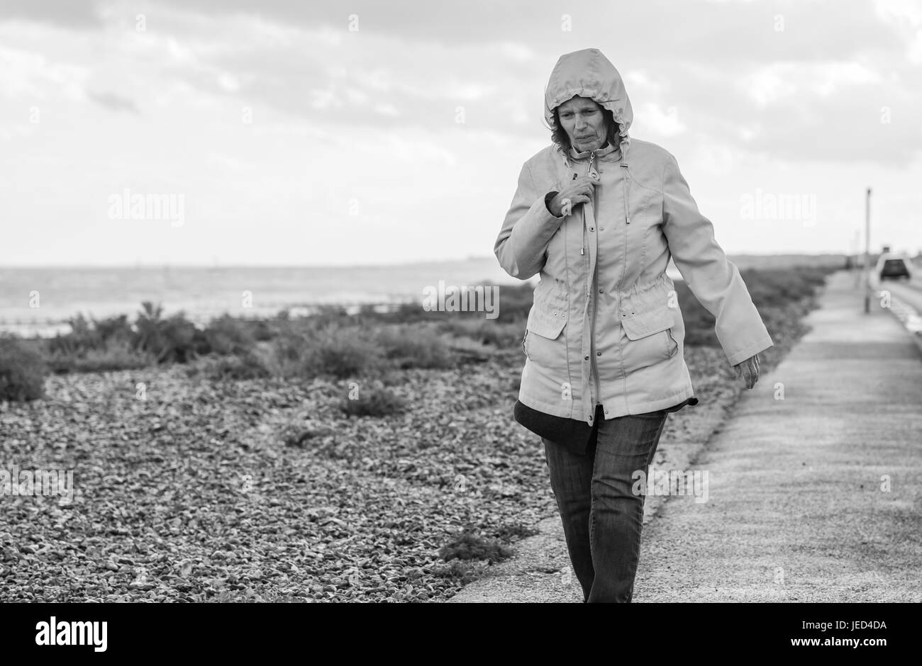 Wet and windy. Lady walking along a seafront road into the wind on a dull day. Black and white image. - Stock Image