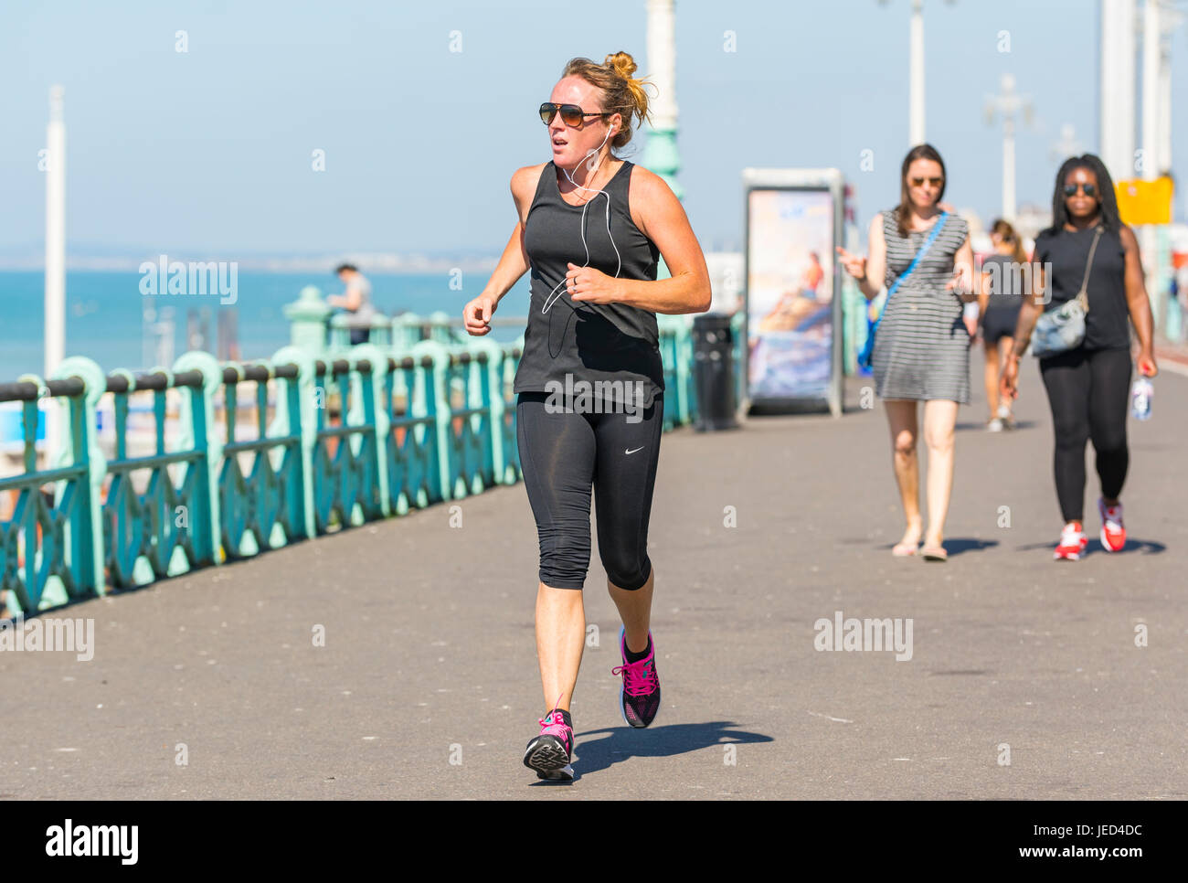 Young woman jogging along the seafront promenade on a hot day in Summer. - Stock Image