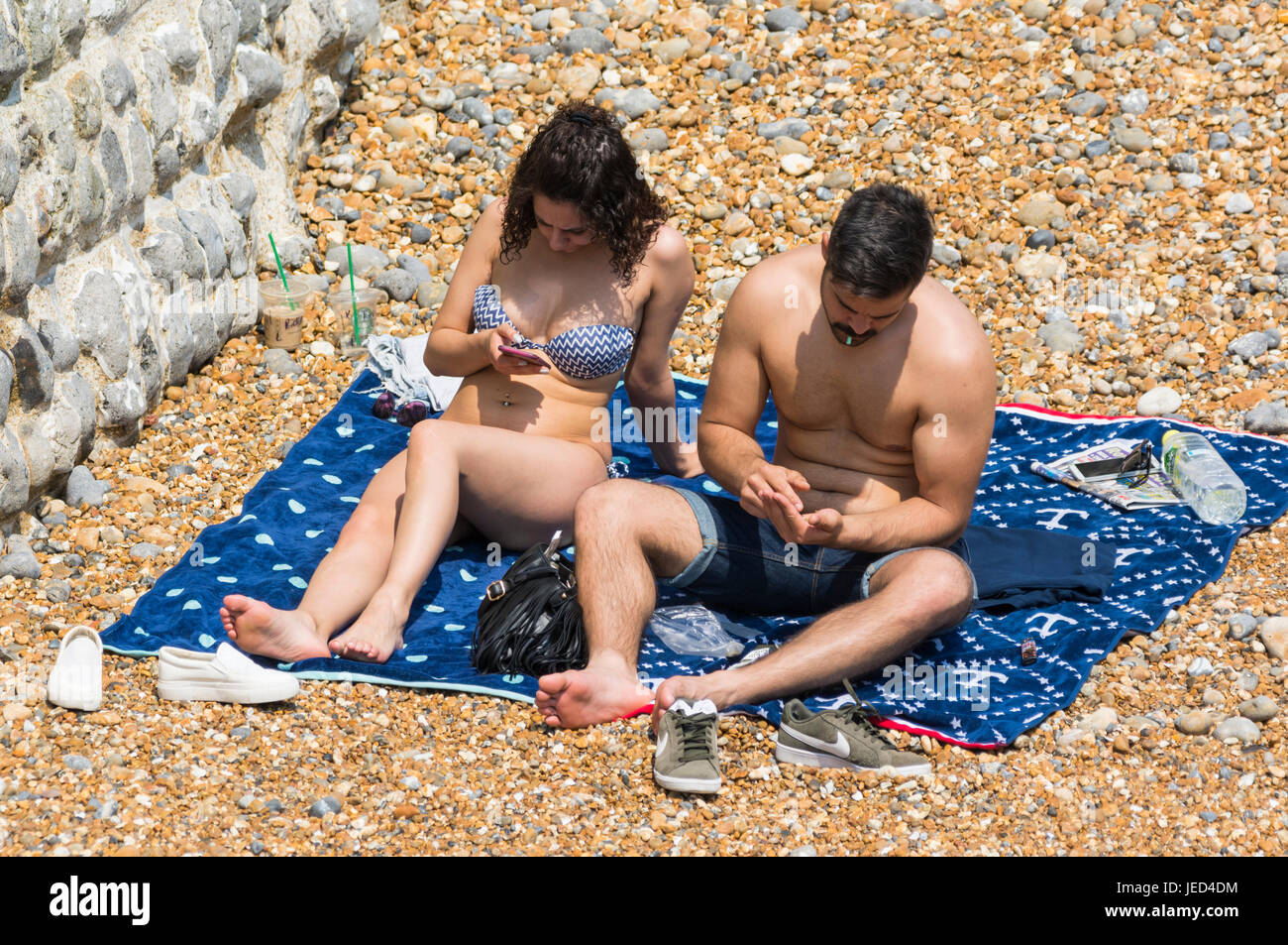 Young couple sunbathing on a beach doing their own thing. - Stock Image