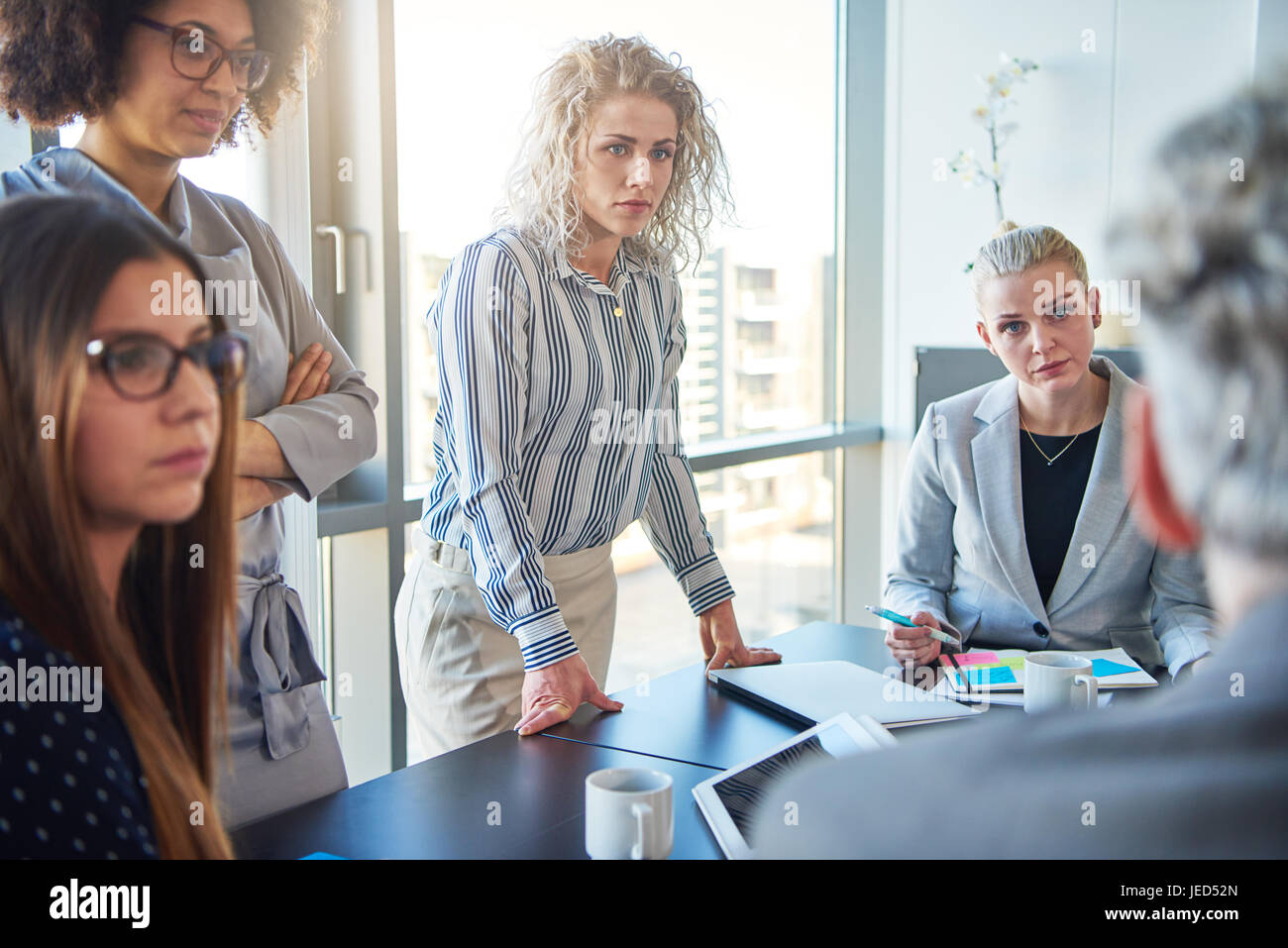 Diverse group of focused colleagues discussing business strategy together during a meeting in an office boardroom - Stock Image