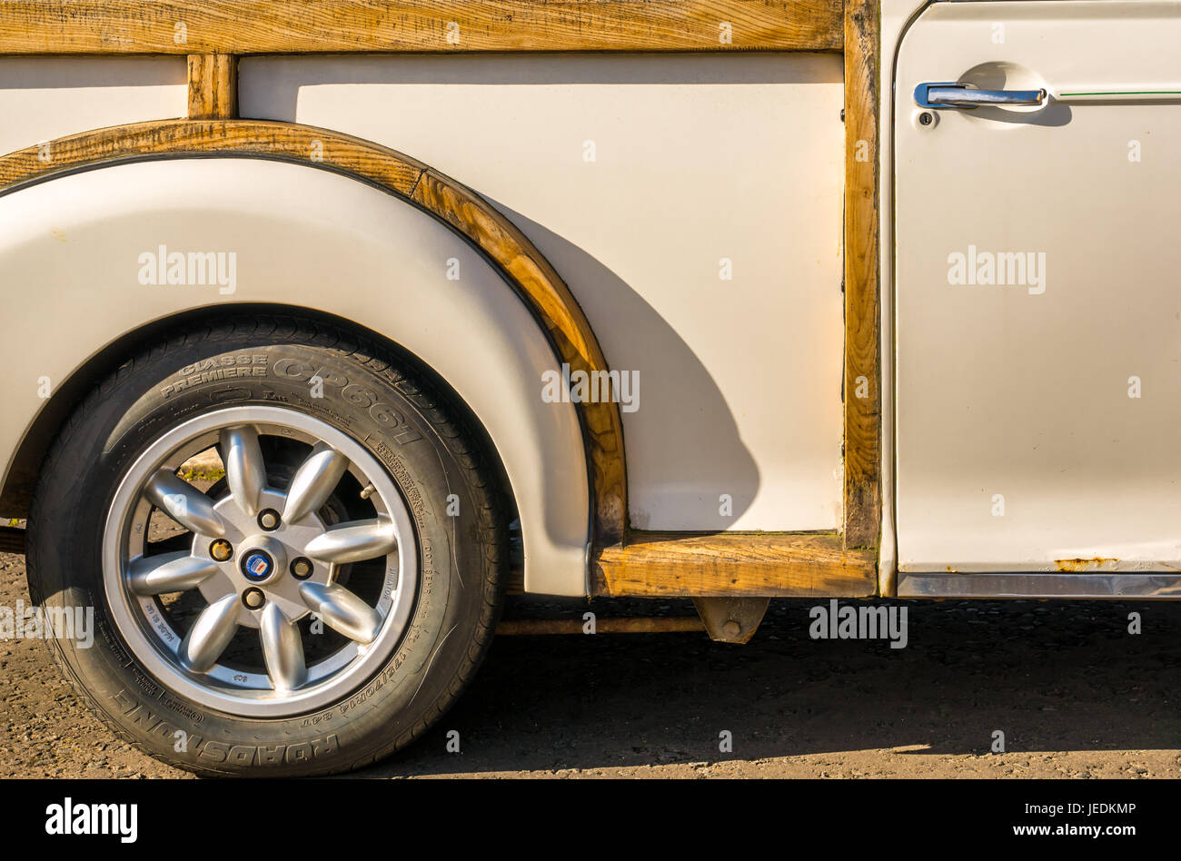 Close up side view of wheel arch, tyre, and door of vintage white Morris Minor Traveller estate car, East Lothian, - Stock Image