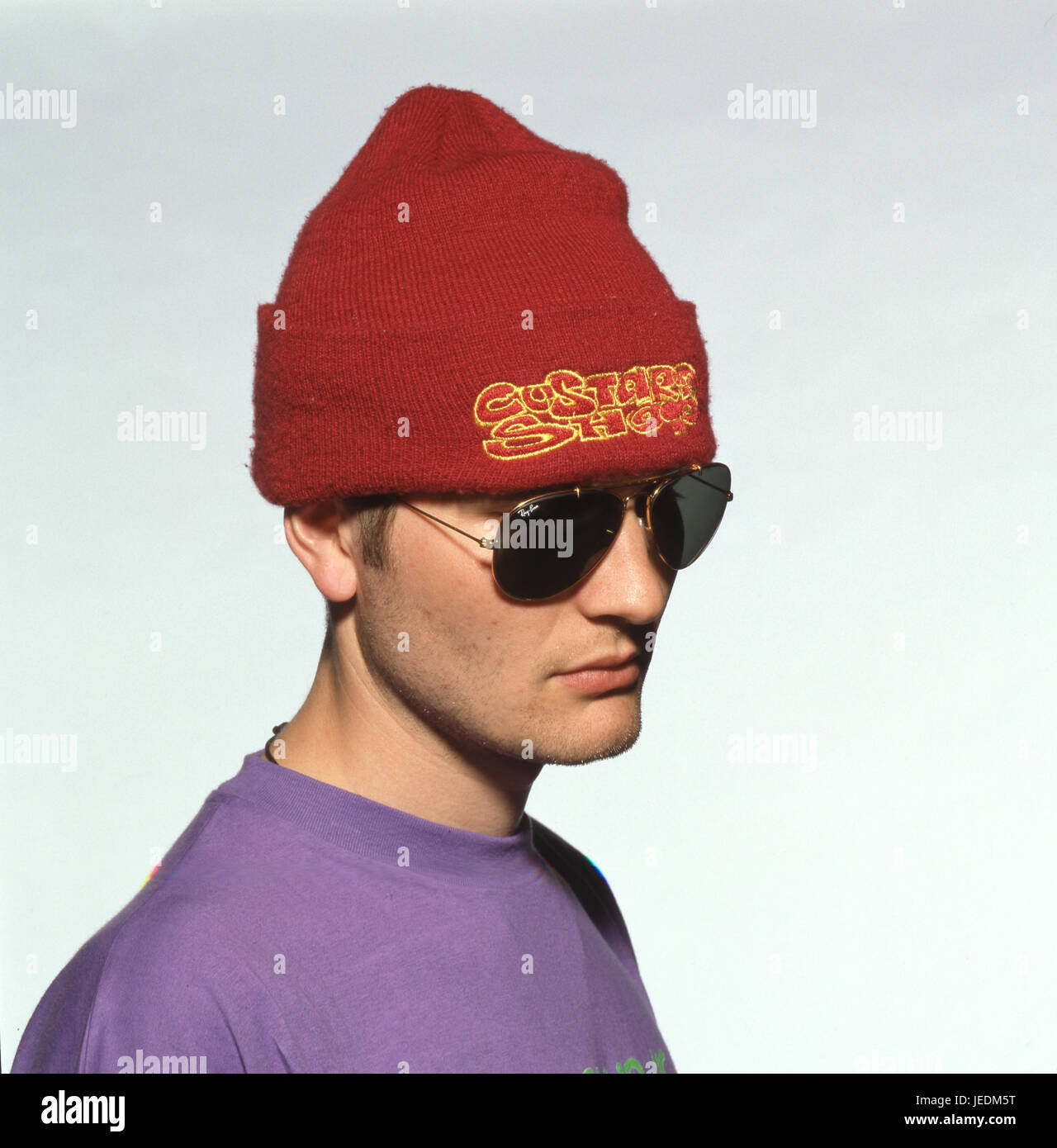 Portrait of a young man in a purple t shirt, wearing a red hat and sunglasses - Stock Image