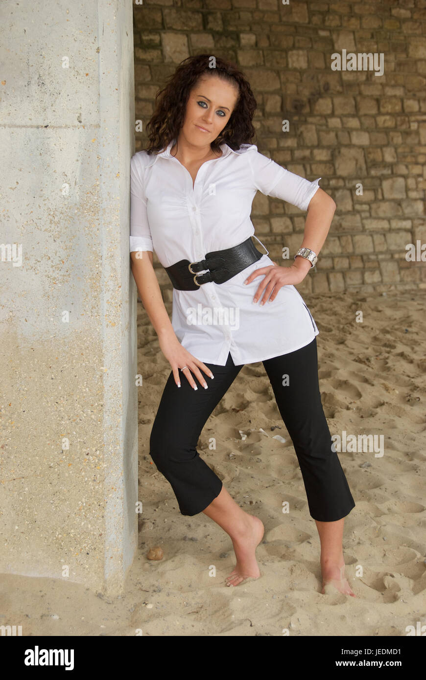 Pretty dark haired girl outdoors wearing a black and white outfit - Stock Image