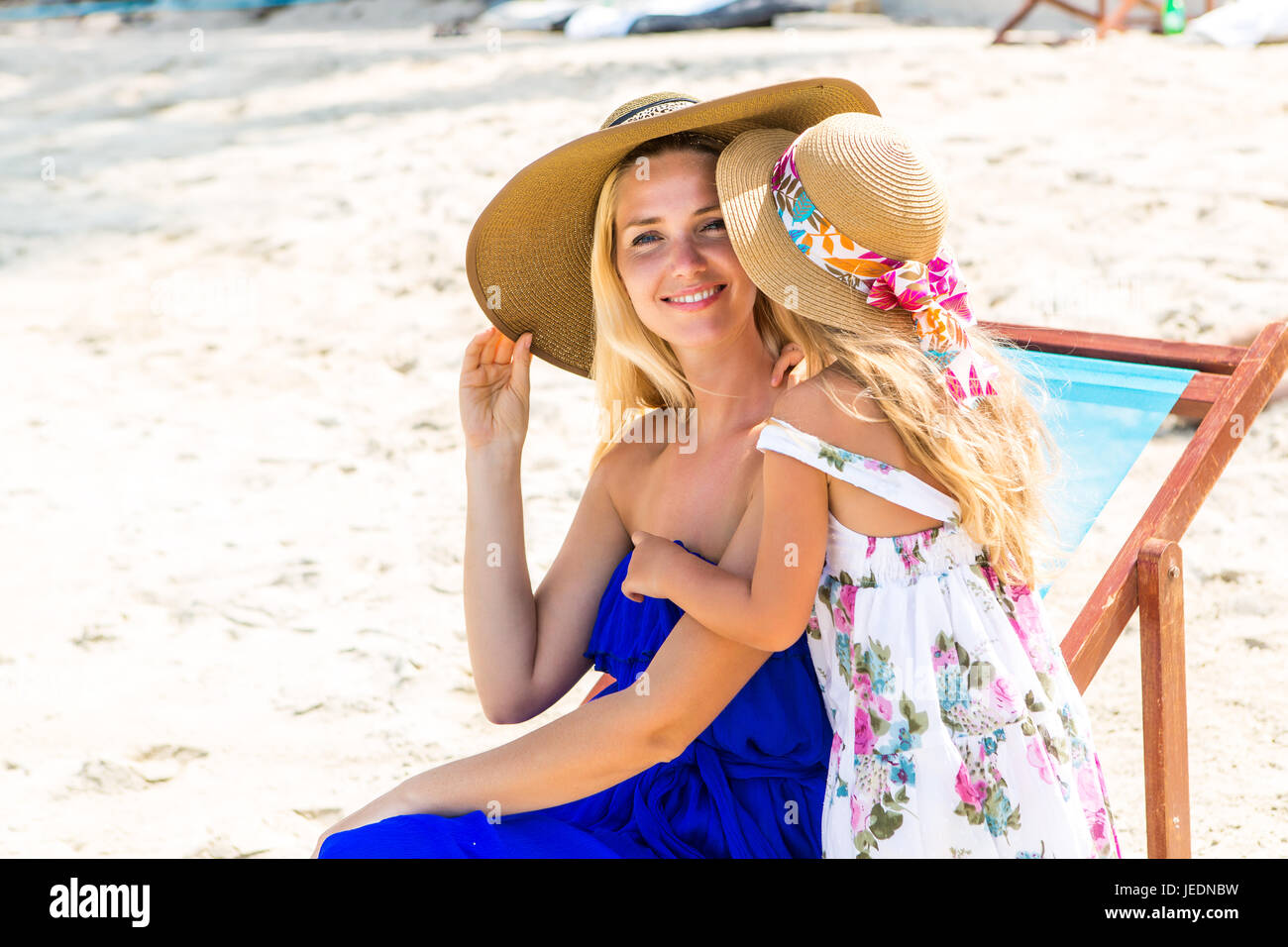 Beautiful mother lady with her pretty blonde cute daughter. Woman sitting in a beach chair, smile and look to camera. - Stock Image