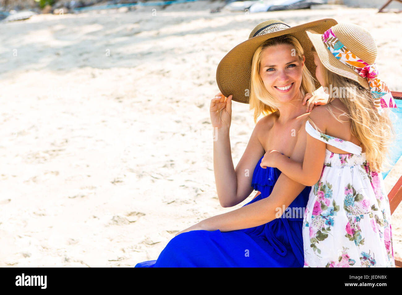 Beautiful mother lady in beach straw hat with her pretty blonde cute daughter. Woman in a beach chair smile to the - Stock Image