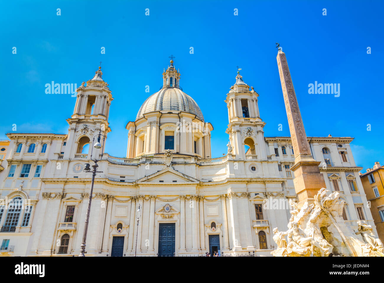 Church Sant Agnese in Agone and Fountain of the four Rivers with Egyptian obelisk on Piazza Navona in Rome, Italy - Stock Image