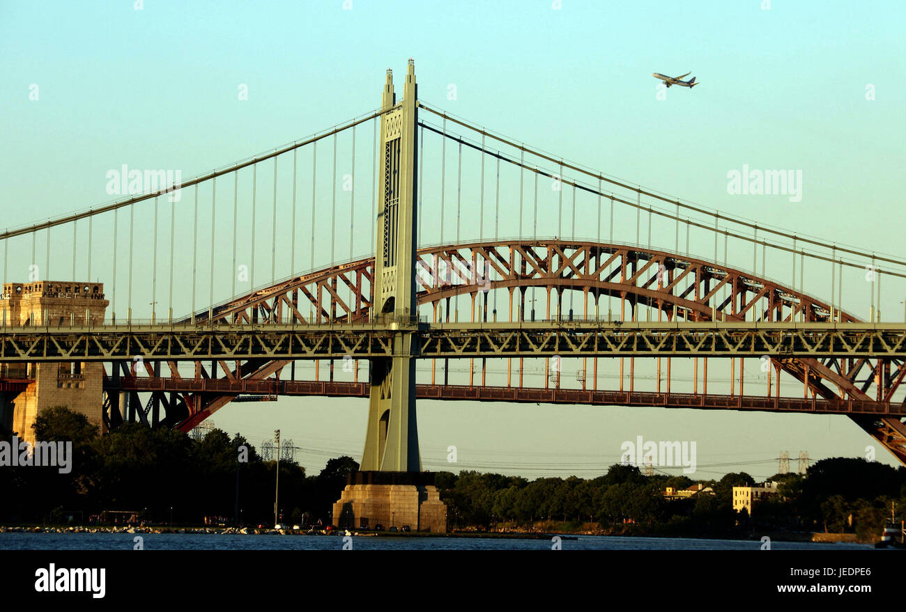 Robert F. Kennedy Bridge, also know as RFK Triborough Bridge, seen at sundown with an ascending jet plane - Stock Image