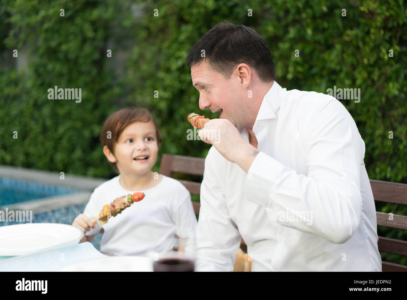 Father with little bcute boy eating barbecue in family lunch time at home. Stock Photo
