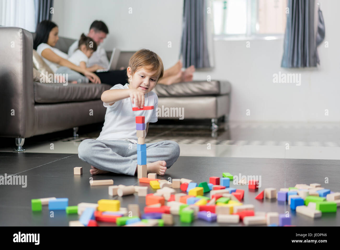 Asian boy playing wood toy in living room with father, mother and daughter in background. Happy family. Stock Photo
