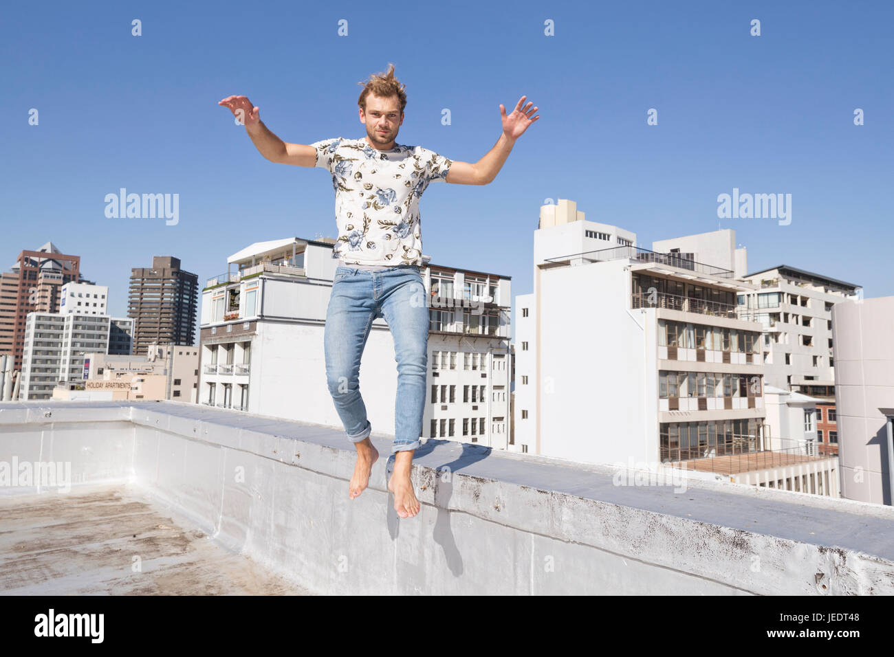 Barefooted man jumping from balustrade of a rooftop terrace - Stock Image