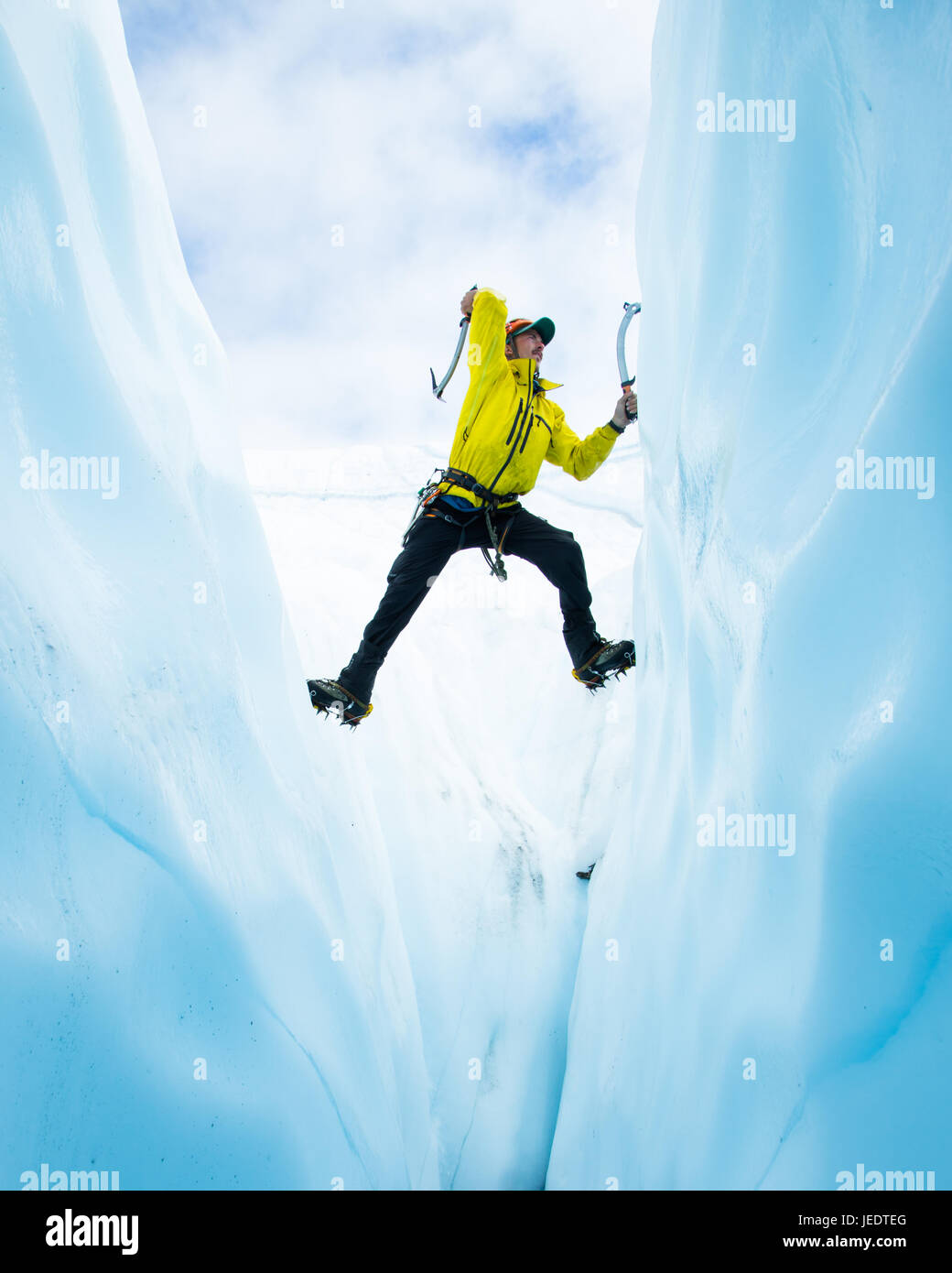Ice climber climbing out of a crevasse on the Matanuska Glacier in Alaska. He is soloing up the span and stemming - Stock Image