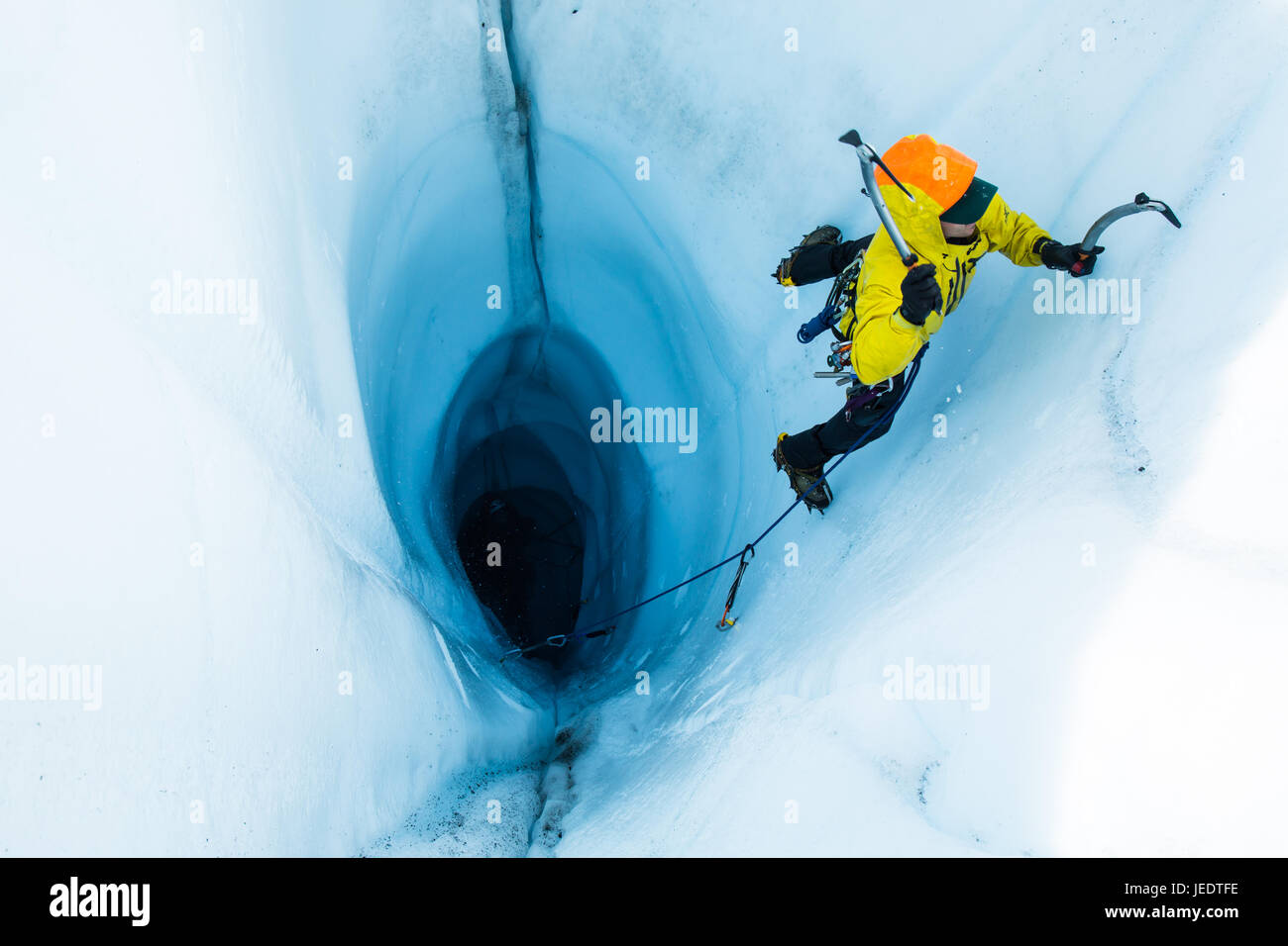 A man leading an ice climb out of a large moulin or hole in the ice of the Matanuska Glacier in Alaska. To start - Stock Image