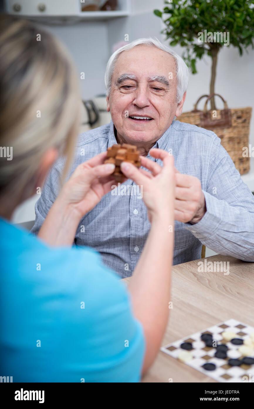 Gereatric nurse doing dexterity games with elderly patient - Stock Image