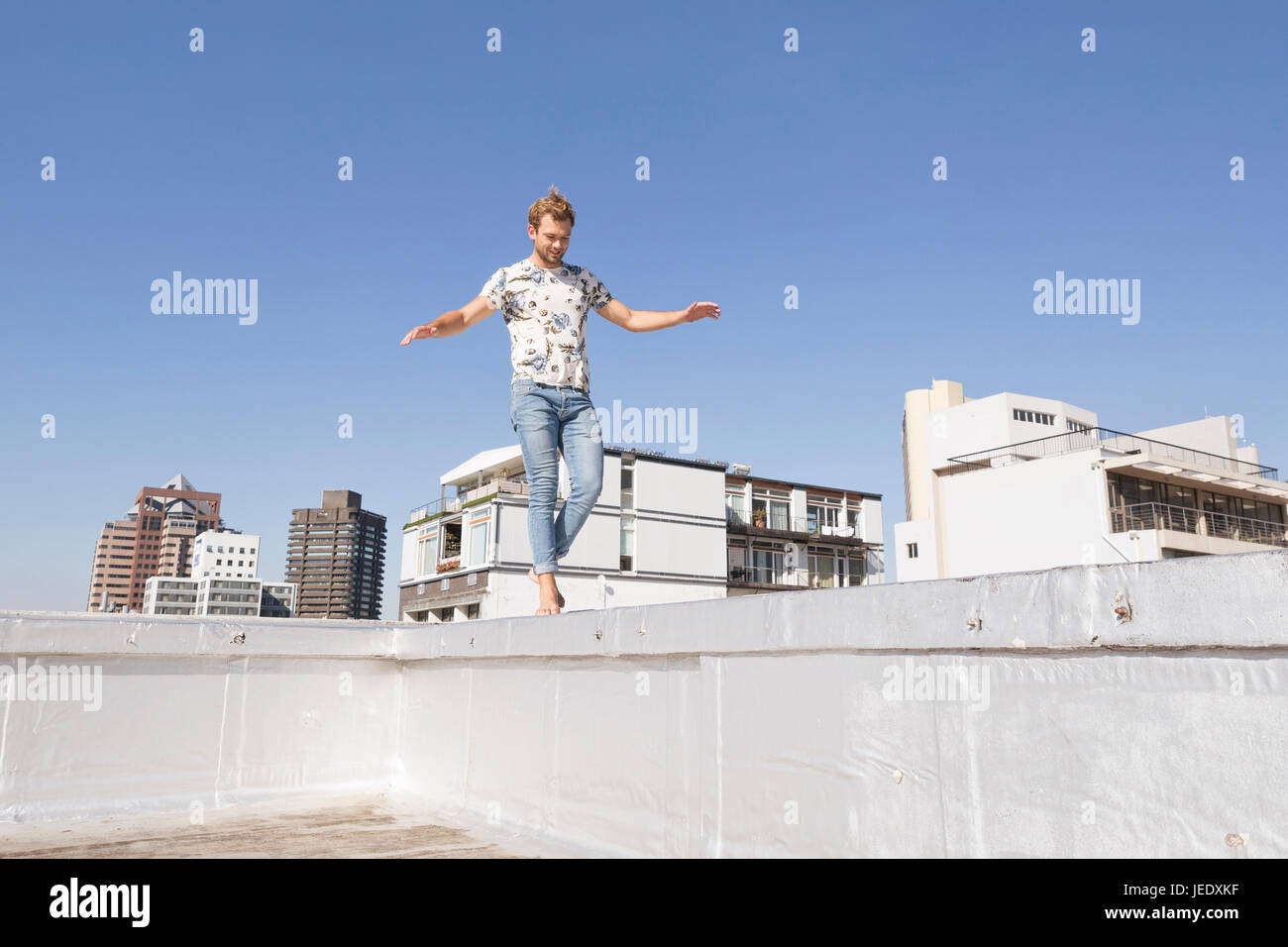 Barefooted man balancing on balustrade of a rooftop terrace - Stock Image