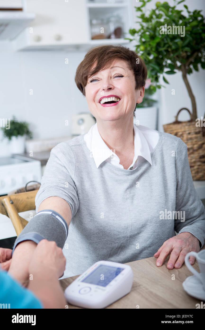 Gereatric nurse measuring blood pressure of patient - Stock Image
