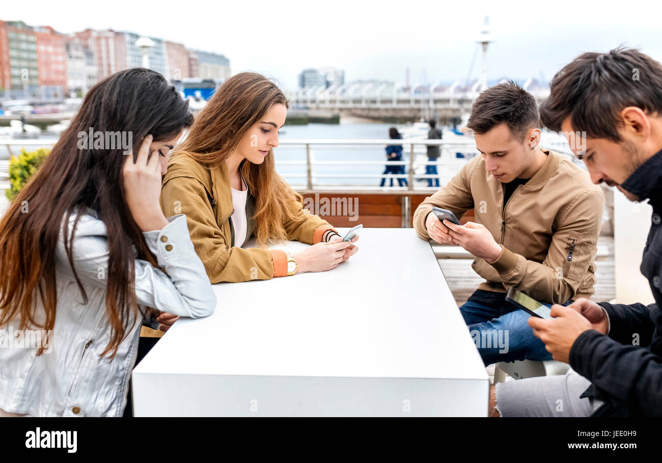 Group of friends using their smartphones - Stock Image