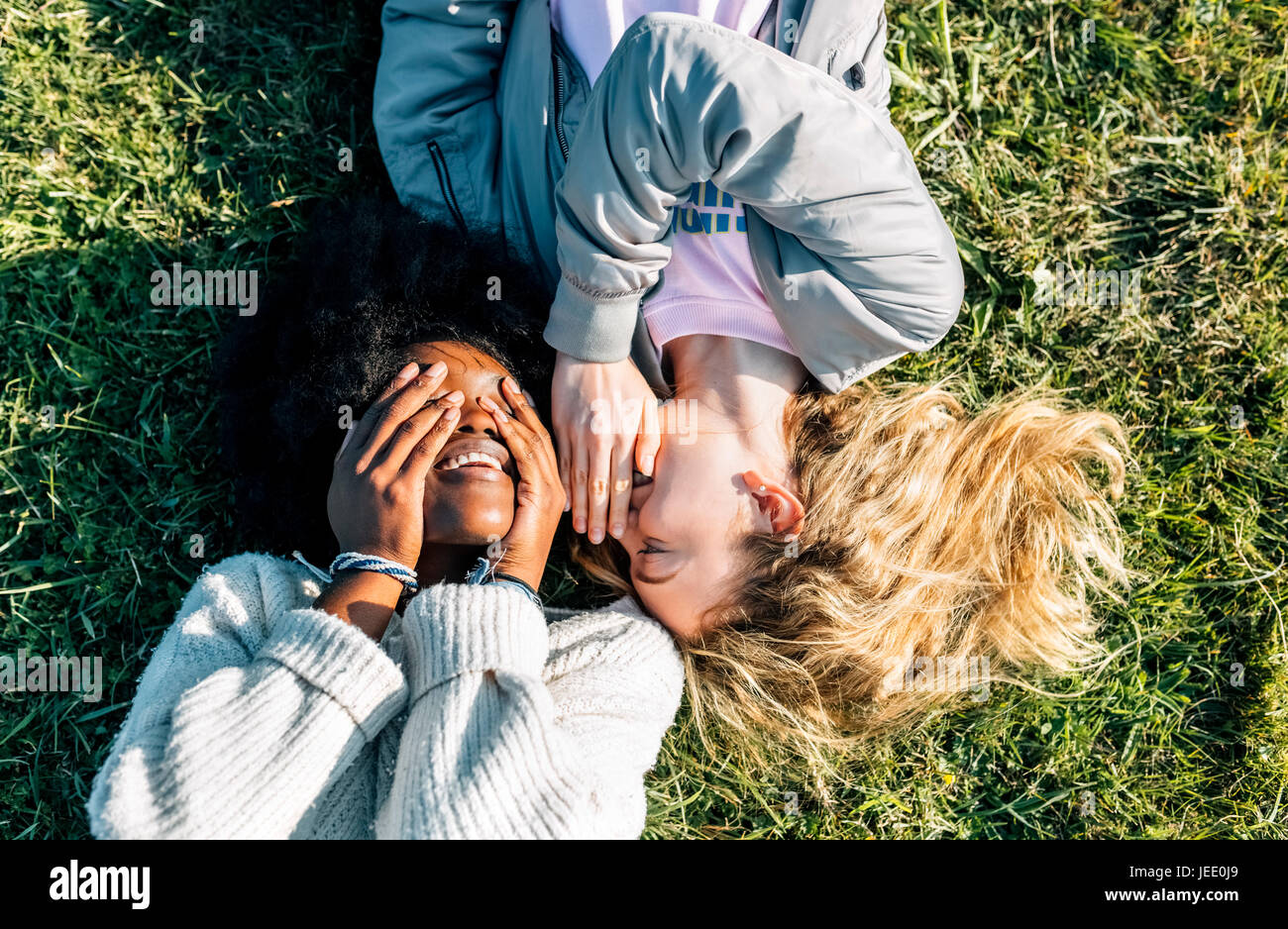 Two best friends telling secrets lying in the grass - Stock Image