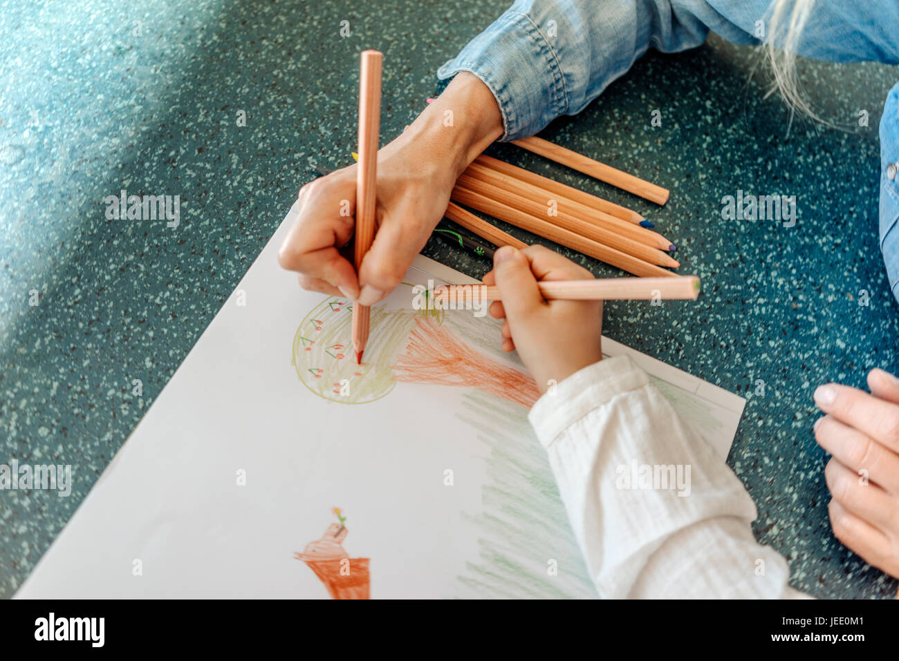 Woman and girl drawing together - Stock Image