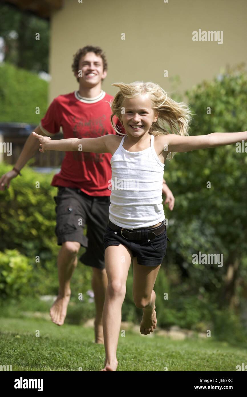 siblings fun boy girl catch play garden meadow person stock