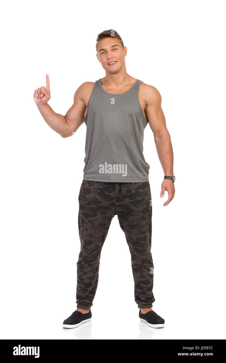 Young muscular man in tracksuit pants with camo, gray tank top and black sneakers standing and pointing up. Full - Stock Image