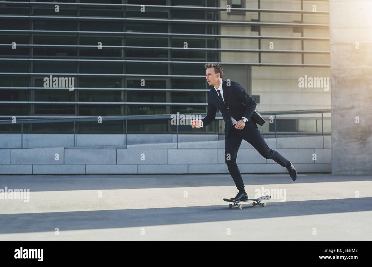 Side view of a businessman in black suit on a skateboard - Stock Image