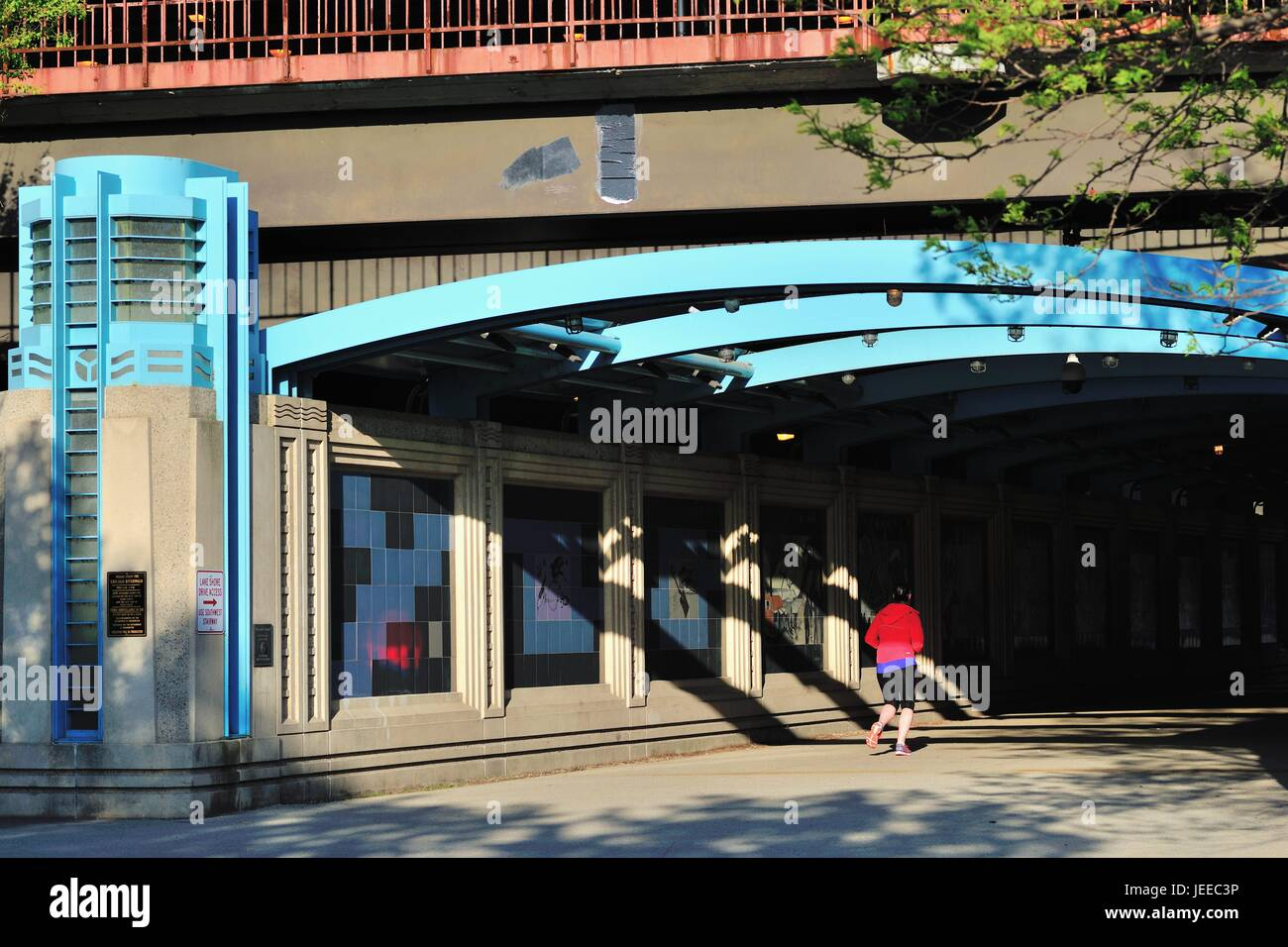 A solitary runner entering an underpass below Chicago's Lake Shore Drive near DuSable Harbor. Chicago, Illinois, Stock Photo