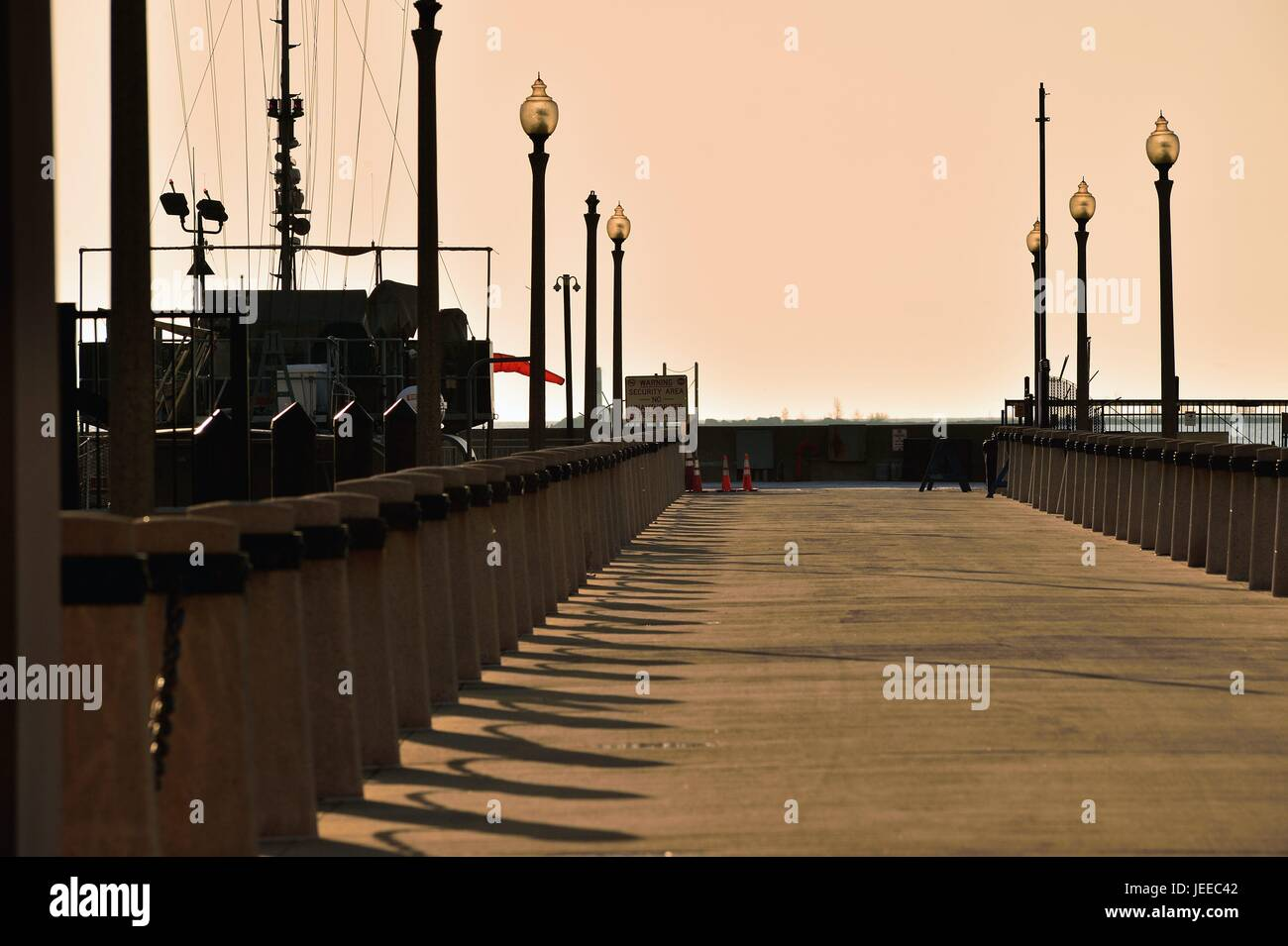 The glow from a spring sunrise both illuminates and creates shadows on a pier near a marina in Chicago's DuSable - Stock Image