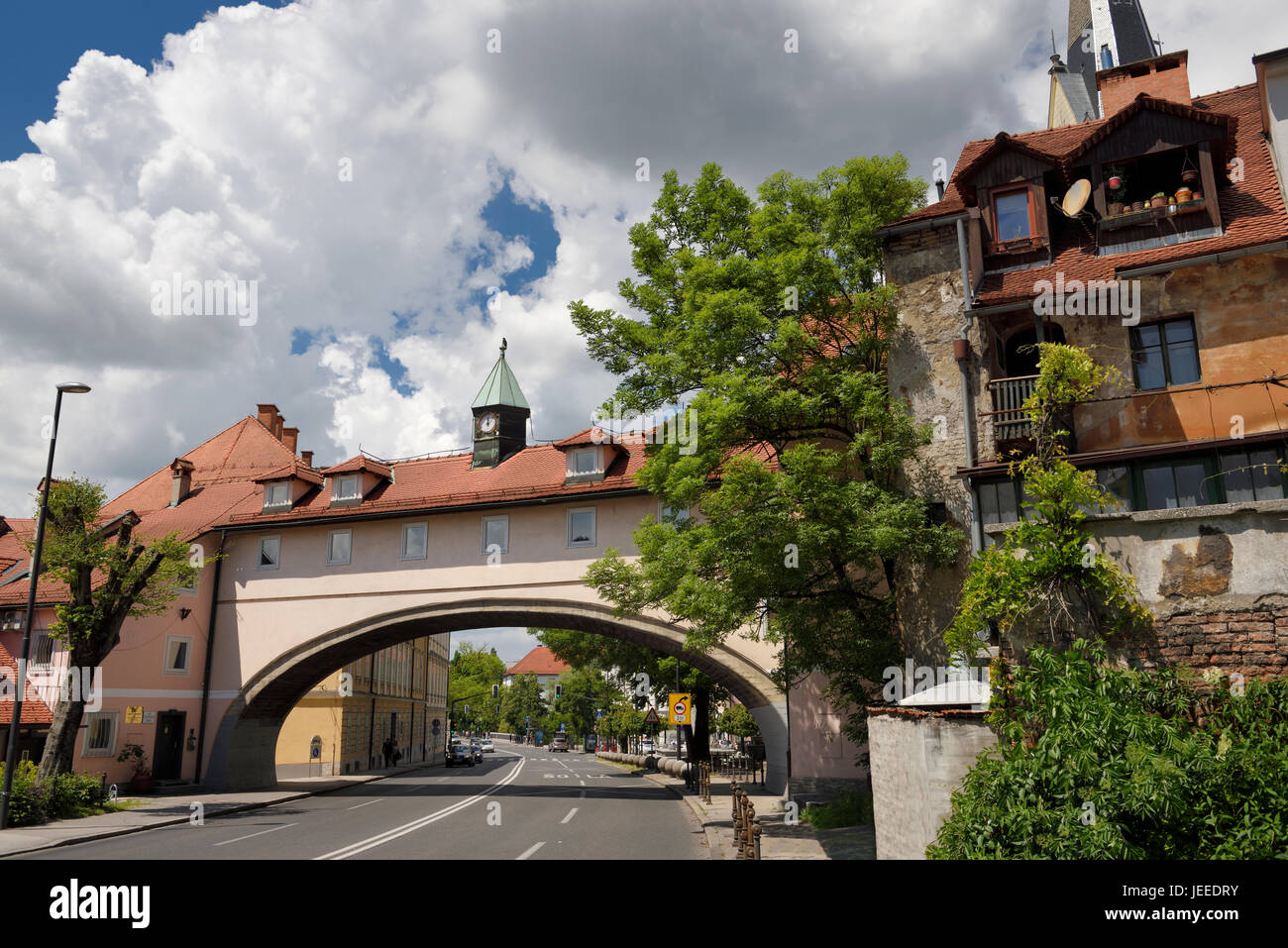 Building arch with rooms and clock tower over four lane Karlovska road with St. James Catholic church belfry Ljubljana - Stock Image