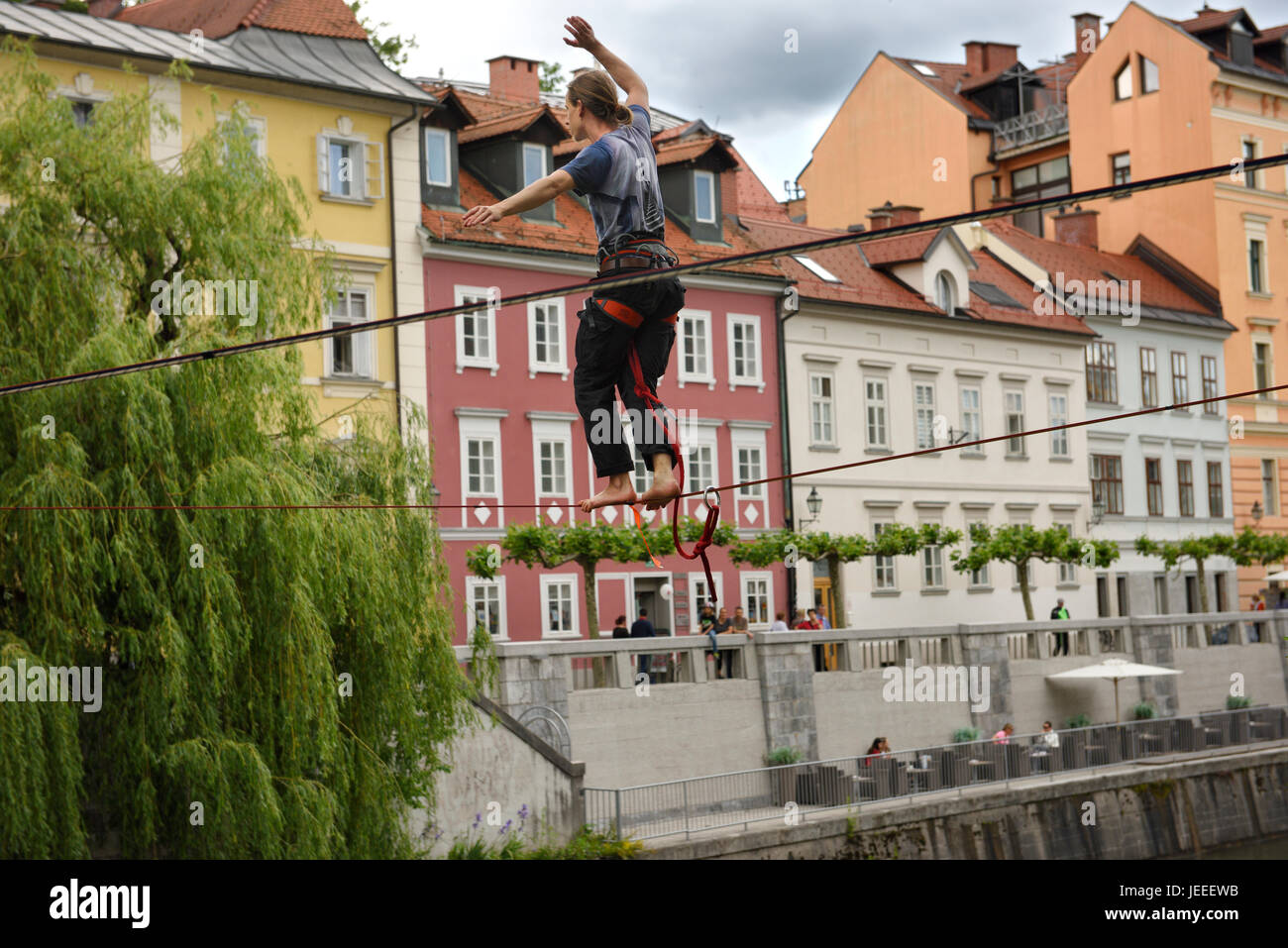 Young man balancing on a slack line high over the Ljubljanica river canal in the old section of Ljubljana Slovenia - Stock Image