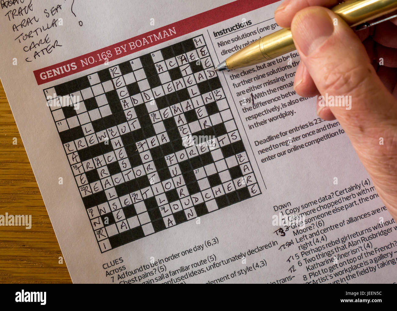 Solving Complicated Crossword Puzzle In The Guardian Newspaper Called Genius By Setter Nom De Plume Boatman With Mans Hand Holding Pen