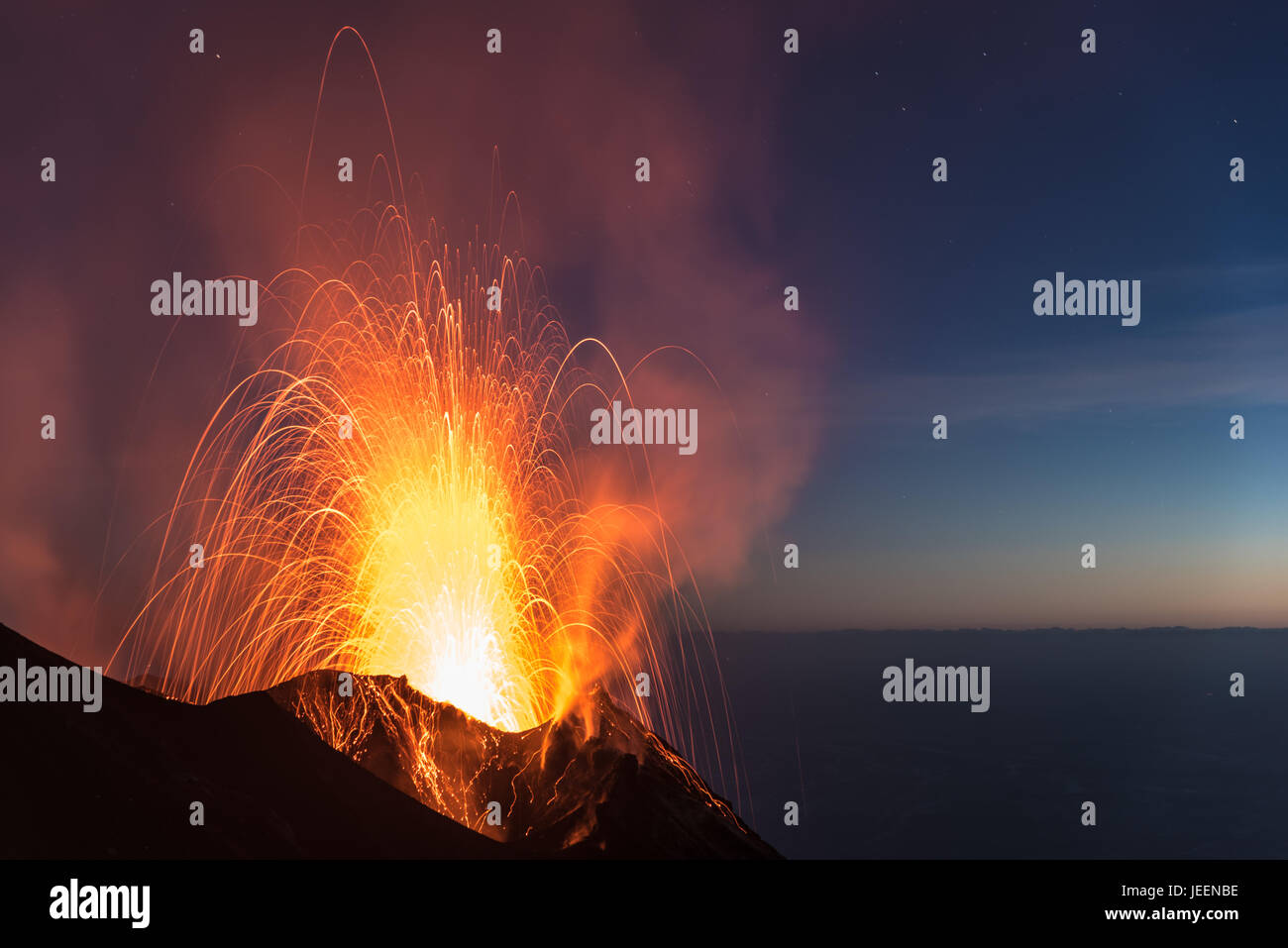 Strong strombolian volcanic eruption from Stromboli volcano (Eolian Islands, Lipari, Italy) at night, craters illuminated - Stock Image