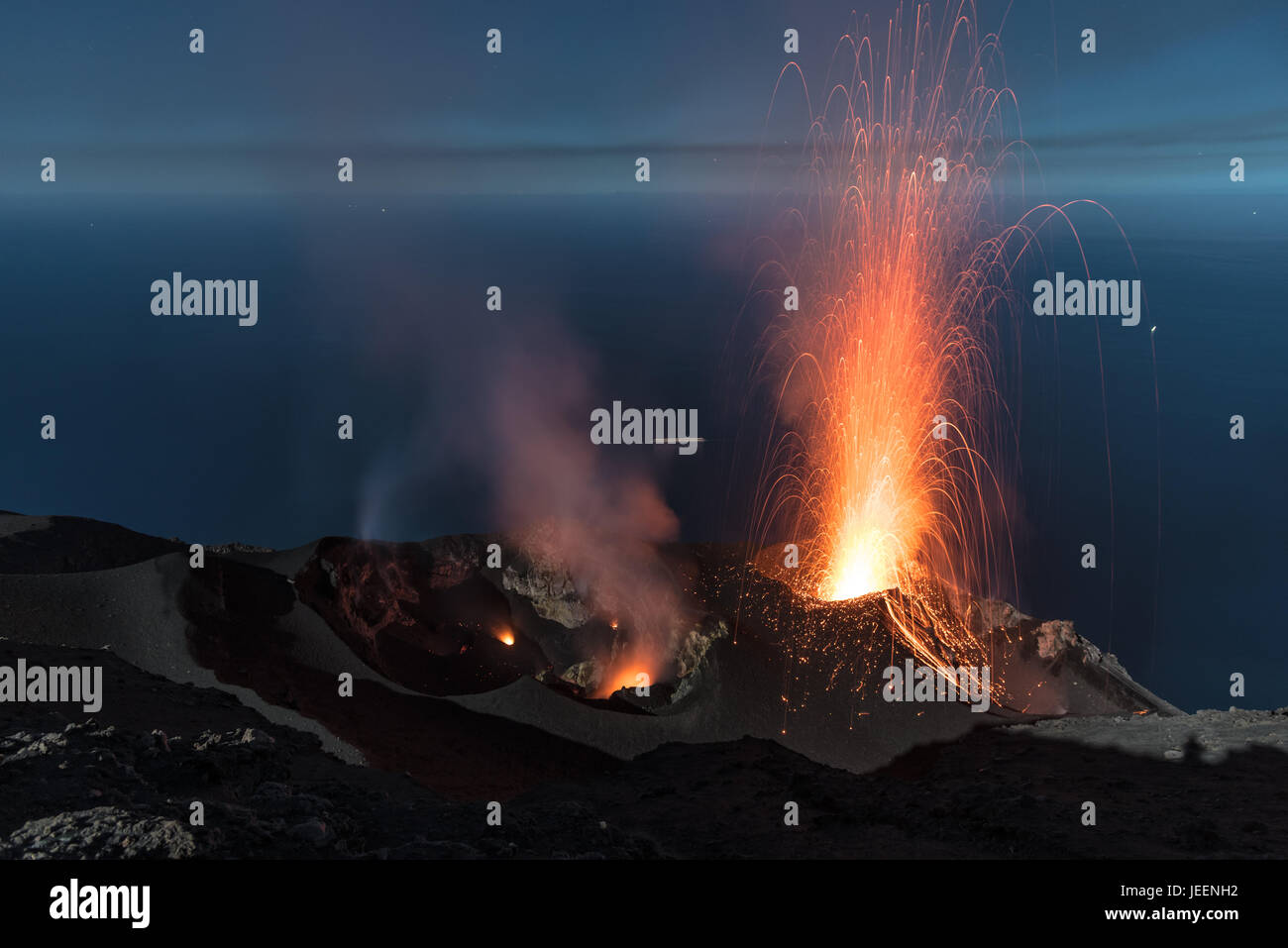 Strong strombolian volcanic eruption from Stromboli volcano (Eolian Islands, Lipari, Italy) at night, craters illuminated - Stock Image
