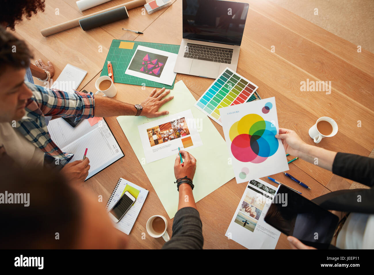 Top view shot of group of creative designers discuss the color palette during meeting. Creative team brainstorming - Stock Image