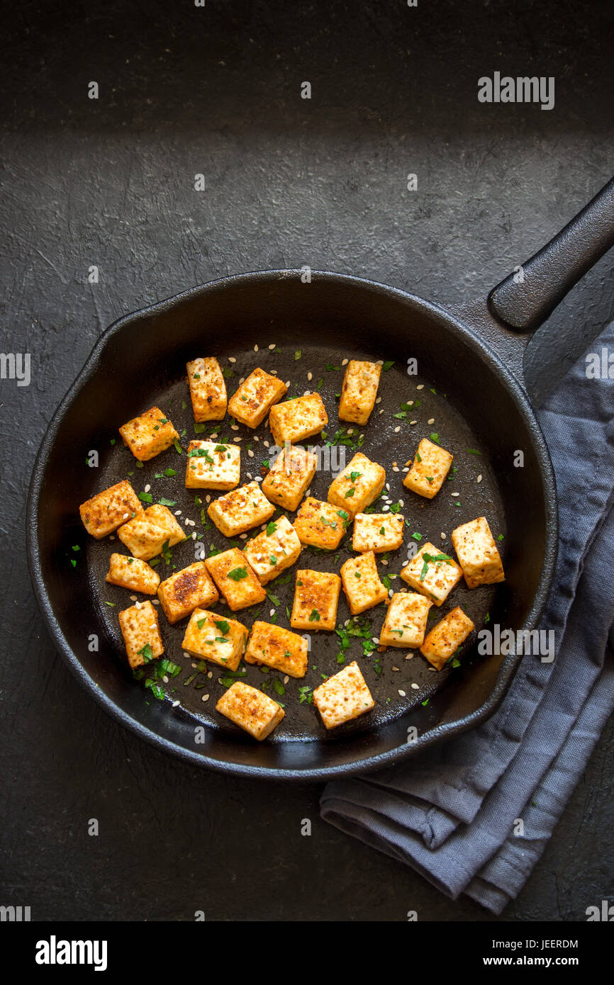 Fried tofu with sesame seeds and spices on cast iron pan, copy space. Healthy ingredient for cooking vegan vegetarian - Stock Image