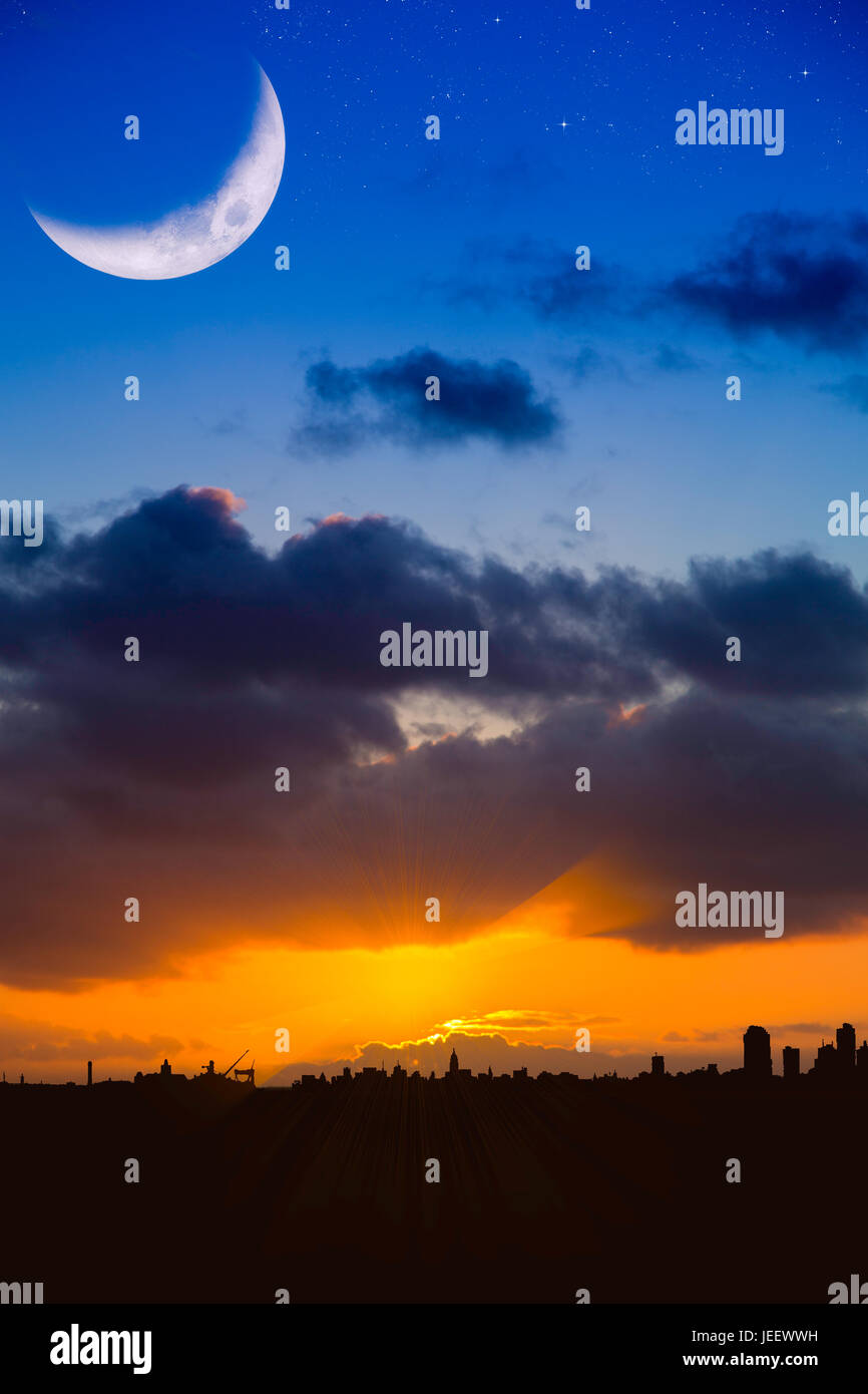 Dramatic blue and orange sky with modern city skyline silhouetted against a stormy. A large moon crecent and stars Stock Photo