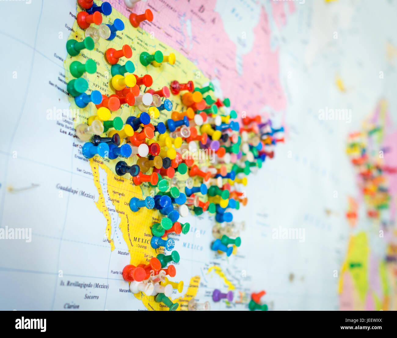 Many colourful pins in a wall map of America The map is hanging on