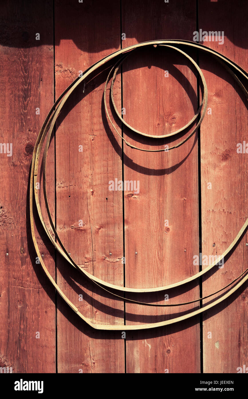 Rural building exterior. Metal circles hanging on wall. - Stock Image