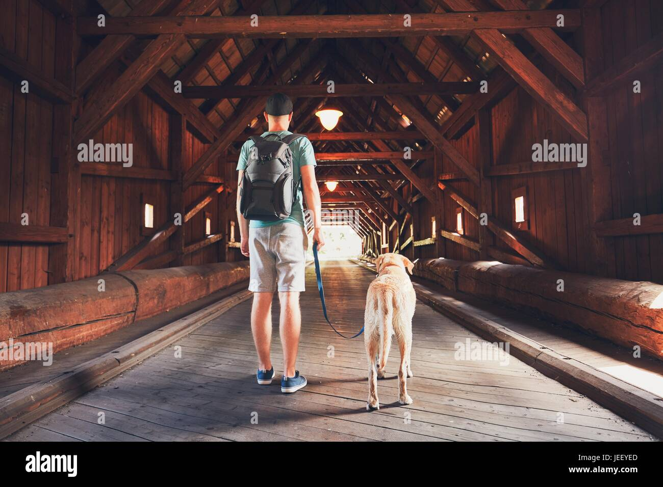 Young tourist with his dog inside of the covered bridge over the river in Radosov, Czech Republic - Stock Image